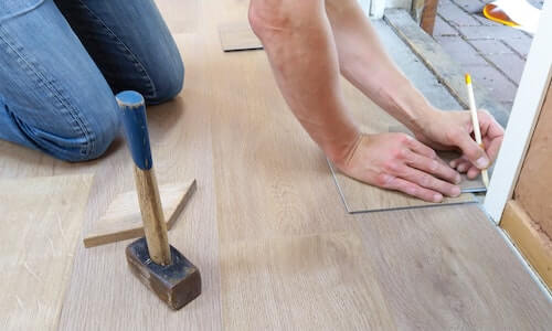 Someone laying wood flooring with a hammer