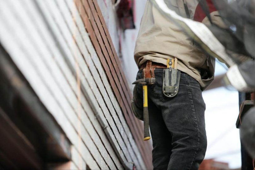 man in beige shirt and jeans and tool belt works on a home